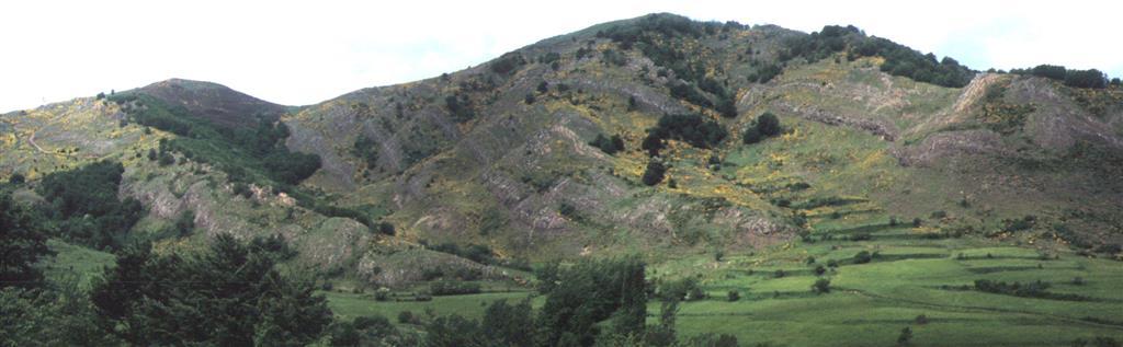 Detalle dúplex de Primajas desde ladera frontal. La capa marrón-rojiza, repetida 7 veces, es la caliza griotte a techo de la Formación Láncara. La Formación Herrería ocupa el cerro más alto, y el pequeño cerro de la izda corresponde a escamas del dúplex de Pardaminos.