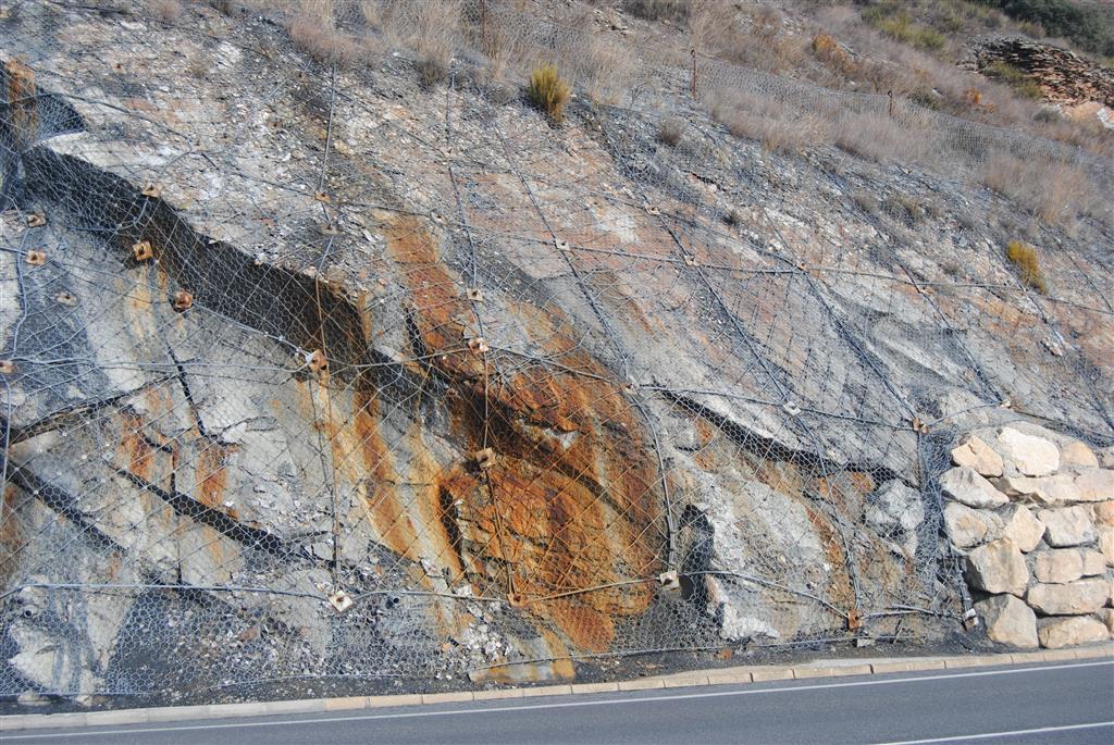 Bulonado y mallado realizado recientemente en el yacimiento silúrico, con objeto de estabilizar el talud de la carretera.