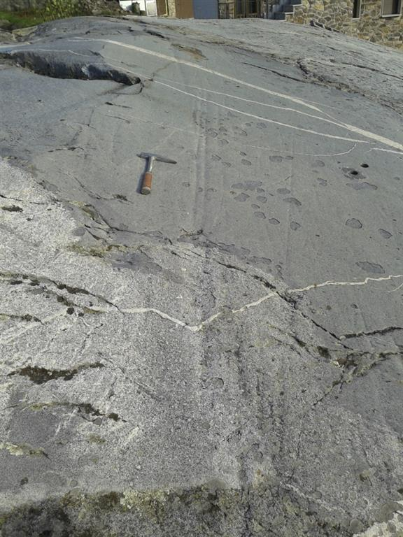 """Roca aborregada de Ribadelago Viejo en la granodiorita de Ribadelago con estrías producidaspor la carga subglaciar y otras huellas de """"plucking""""."""