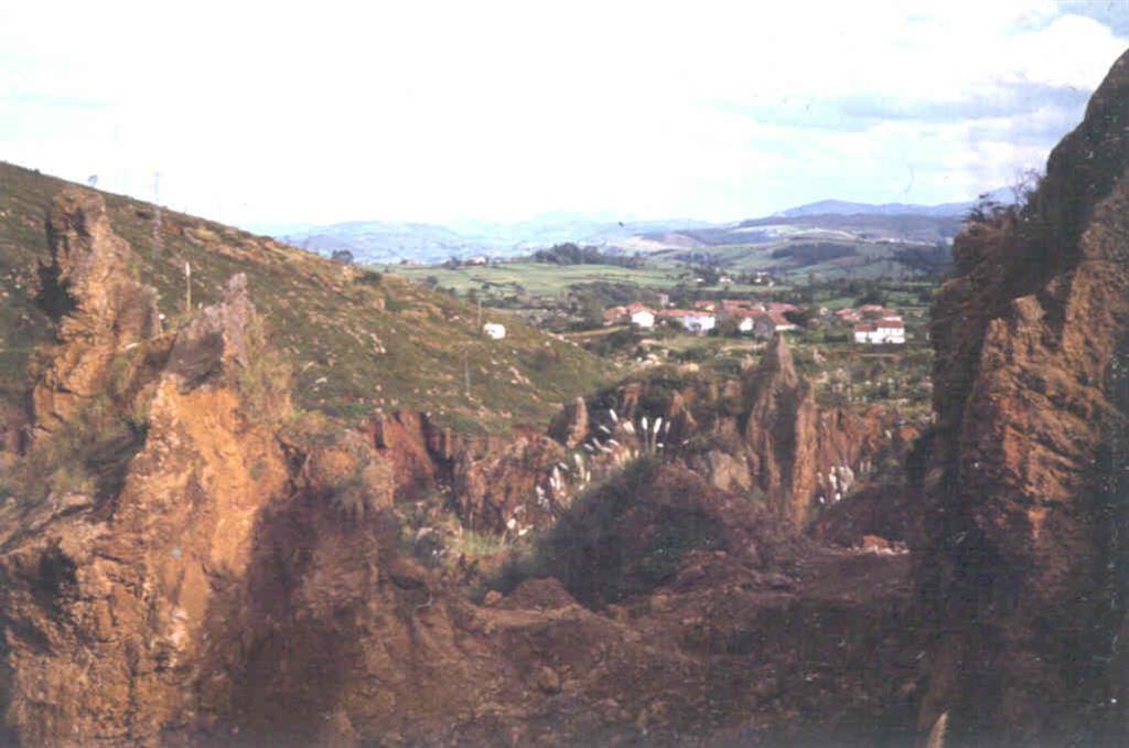 Explotación de Óxidos de Fe en las arcillas de descalcificación. Al fondo, el pueblo de Cabárceno.