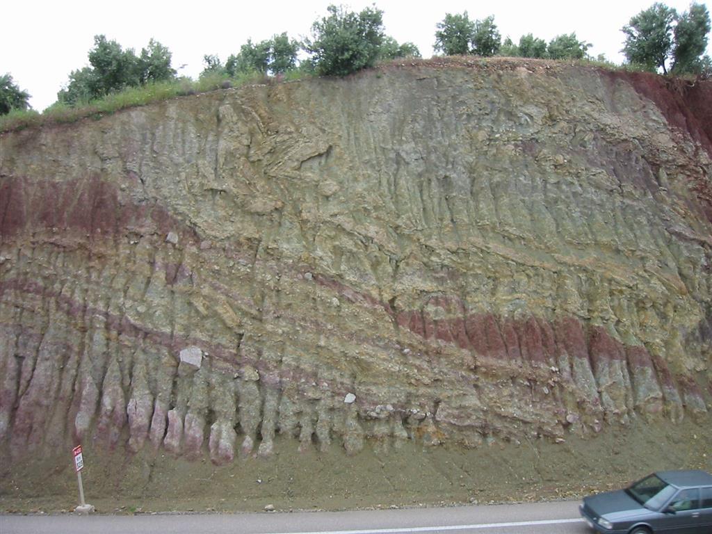 Ciclos depósito tipo flujos de cantos (debris-flow), estratos o paquetes deslizados (slab). Deformación y vuelco de estratos tipo slumping. Cantos angulosos formados por materiales mesozóicos. Granoselección inversa debida a tamización cinética