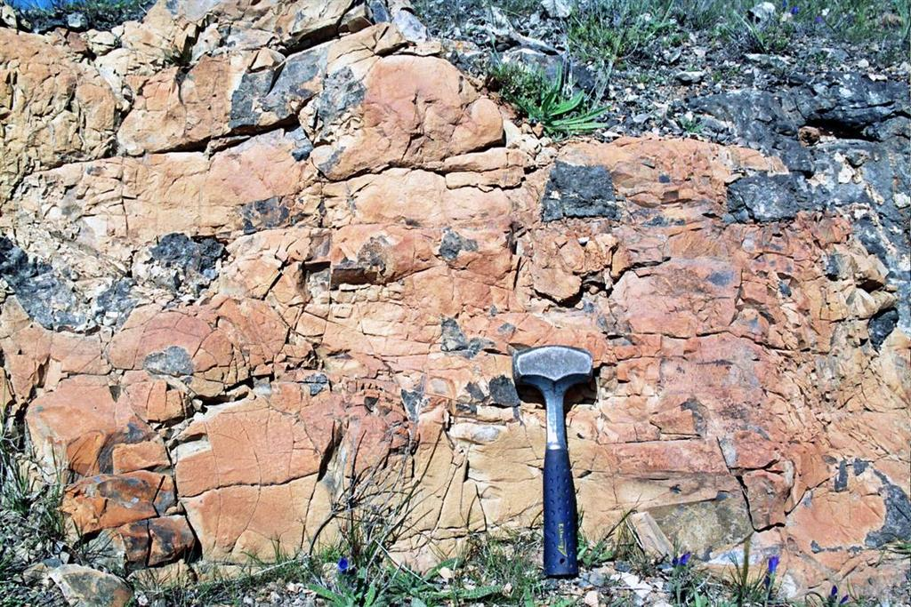 Fragmentos negruzcos de lava en diques peperíticos de sedimentos margosos inyectados en coladas veríticas