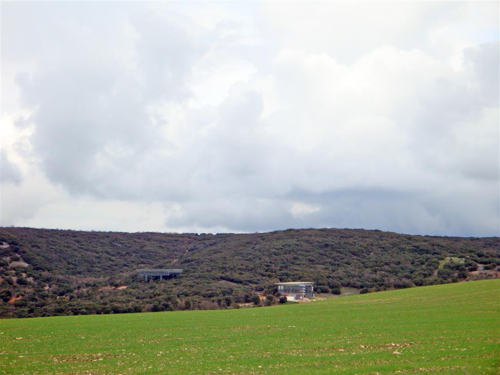 Panorámica desde la pista de acceso al yacimiento desde Ibeas de Juarros. Se observa la instalación para la recepción de visitantes a la derecha y los andamios para acceder a Gran Dolina.