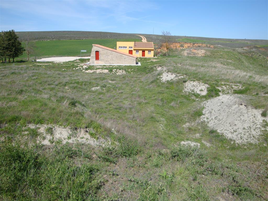 Vista general del museo y del yacimiento paleontológico. En primer plano se distinguen las capas de margas grises de la Unidad de Ambrona, formadas en ambiente palustre-lacustre.