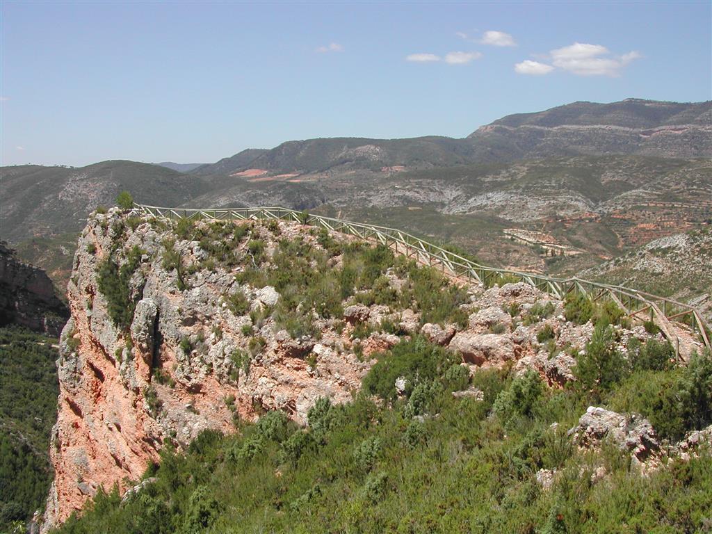 (676.085, 4.382.773). Vista hacia el suroeste del recorrido por la cresta rocosa de conglomerados terciarios desde la parada III-2 a la parada III-1. Al fondo, bloques tectónicos levantados y hundidos de la fosa de Chera (gris Cretácico y rojizo Terciario).
