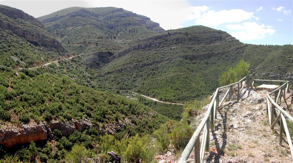 (676.033, 4.382.772). Vista hacia el SSW de la senda por la cresta rocosa de conglomerados terciarios desde la parada III-2 a la parada III-1. Al fondo, la serie del Cretácico inferior y superior de la Fuente de la Puerca mostrando los ciclos sedimentarios y las principales unidades.