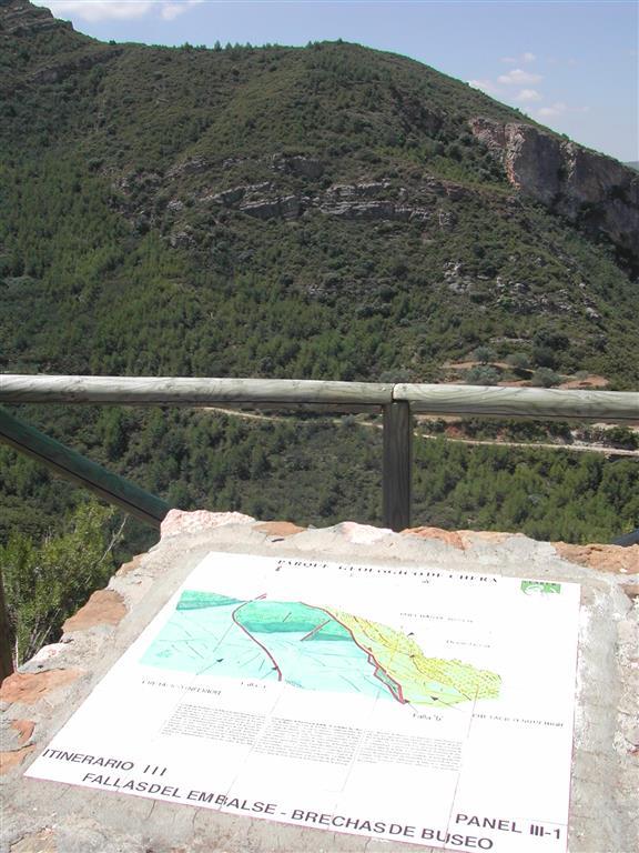 (676.007, 4.382.739). Vista desde el panel correspondiente a la parada III-1 del itinerario por el Parque Geológico de Chera, con explicación de la falla del embalse del Buseo, que limita el relleno terciario de la fosa a la derecha, de las unidades del Cretácico del LIG IB225 a la izquierda.