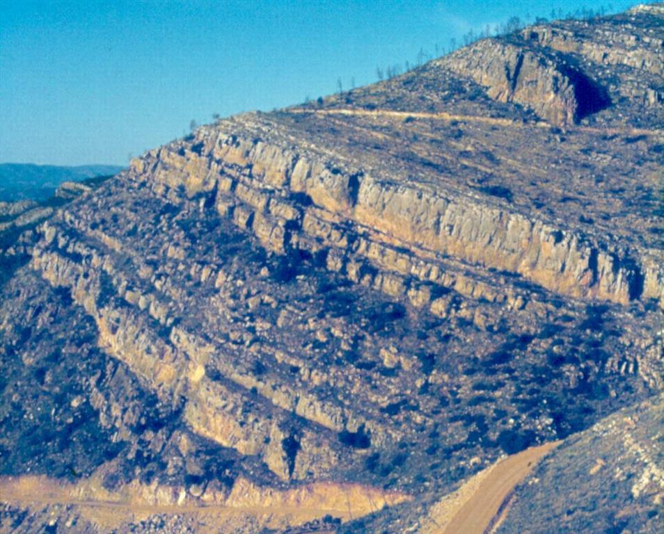 Vista hacia el norte de la sucesión sedimentaria (Fms. Areniscas de Sácaras, Calizas de Aras de Alpuente, Margas de Chera, Dolomías de Alatoz y Dolomías tableadas de Villa de Ves) Albiense – Cenomaniense.