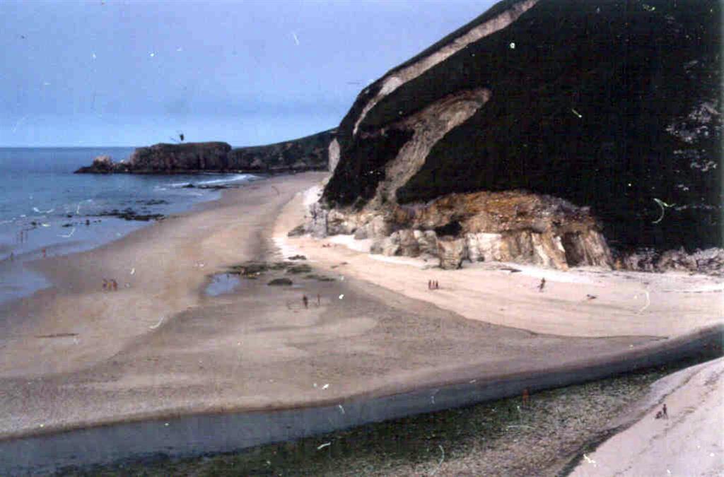 Cuarcita Armoricana (Ordovícico) desembocadura del Río Bedón. Al fondo calizas carboníferas.