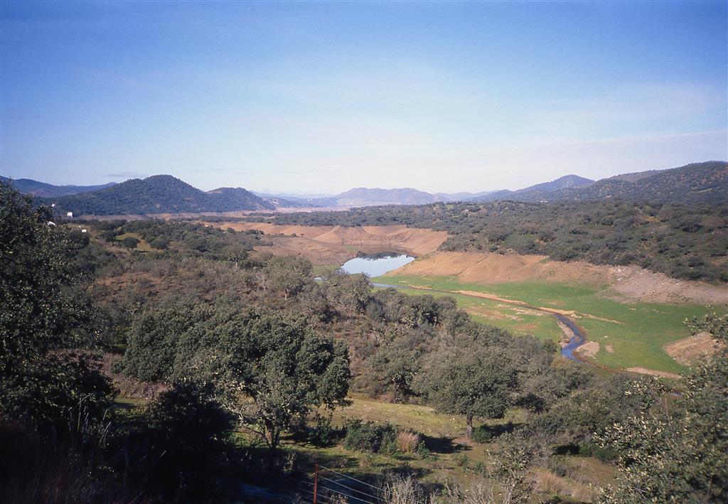 Panorámica hacia el oeste del núcleo Silúrico-Devónico del sinclinal del Valle, con el embalse de El Pintado en periodo de estiaje.